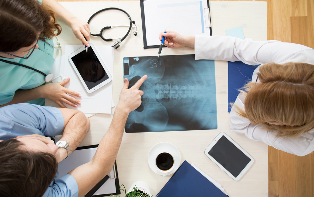 Orthopedic surgeons looking at patient x-ray